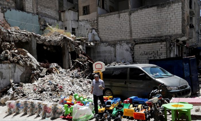 A street vendor sells toys next to rubble of damaged buildings in the city of Idlib, Syria May 25, 2019. (Khalil Ashawi/Reuters)