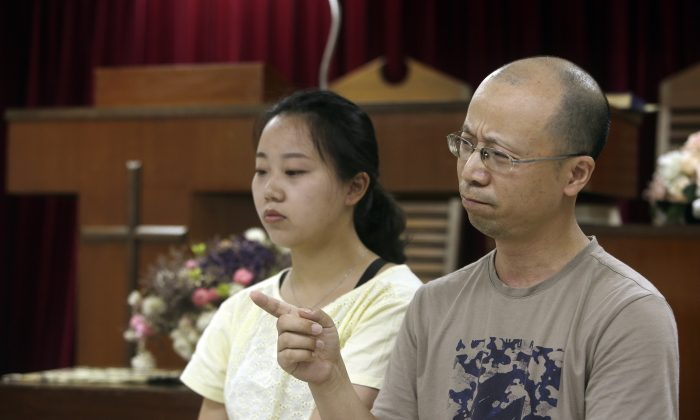 Liao Qiang, right, and his daughter Ren Ruiting speak during an exclusive interview with The Associated Press at a church in Taipei, Taiwan on July 7, 2019. (Chiang Ying-ying/AP)