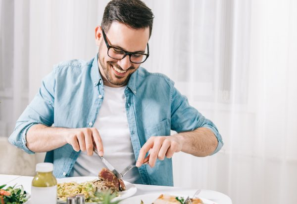 Man eating healthy food and drink detox juice. (Shutterstock)