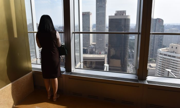File footage of a woman looking out a building in China. (Greg Baker/AFP/Getty Images)