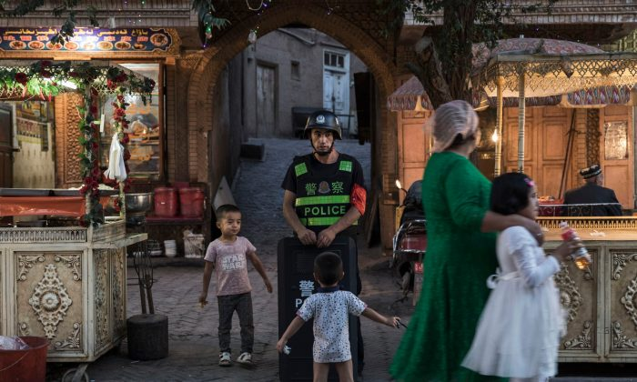 Ethnic Uyghur children joke as they taunt a local police officer in the old town of Kashgar, in the far western Xinjiang province, China, on June 29, 2017. (Kevin Frayer/Getty Images)