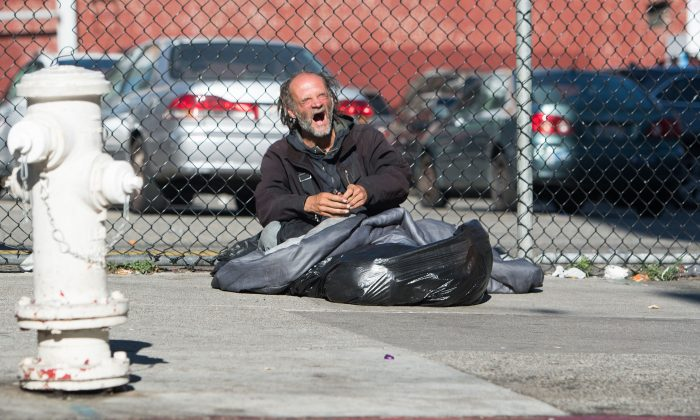 A homeless man yawns along a sidewalk in downtown San Francisco on June 27, 2016. (JOSH EDELSON/AFP/Getty Images)