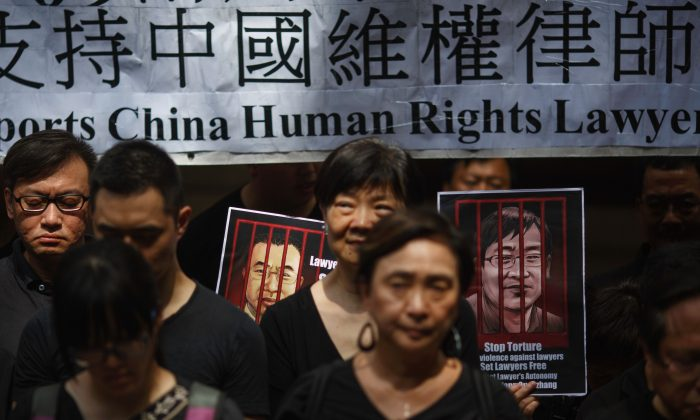 Portraits of detained Chinese human rights lawyers Jian Tianyong (L) and Wang Quanzhang are seen as Hong Kong pro-democracy activists observe a silent protest in support of human rights lawyers in China, outside the Court of Final Appeal in Hong Kong's Central district on July 9, 2017. Dozens gathered outside the Court of Final Appeal as they observed 7 minutes and 9 seconds of silence in solidarity with human rights lawyers in China in remembrance of the July 9, 2015 crackdown. / AFP PHOTO / TENGKU Bahar        (Photo credit should read TENGKU BAHAR/AFP/Getty Images)