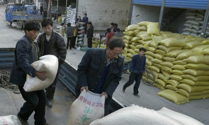 Chinese workers load sacks of grain from a warehouse at a grain market in Kaifeng, Henan Province, China on Feb. 13, 2005. (Mark Ralston/AFP/Getty Images)