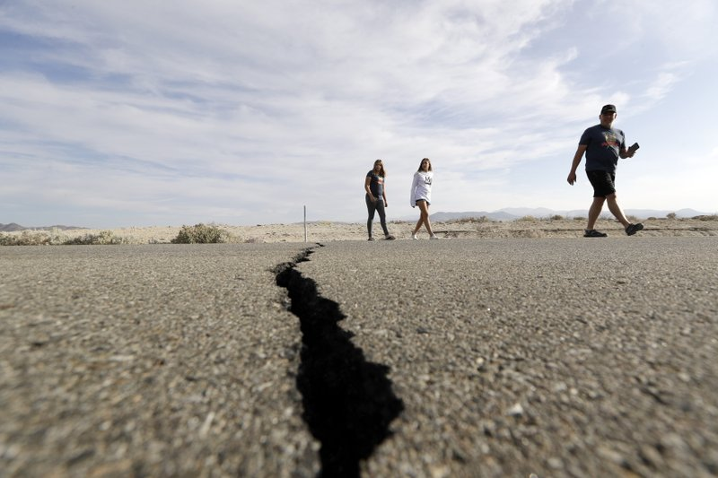 Visitors cross highway 178 next to a crack