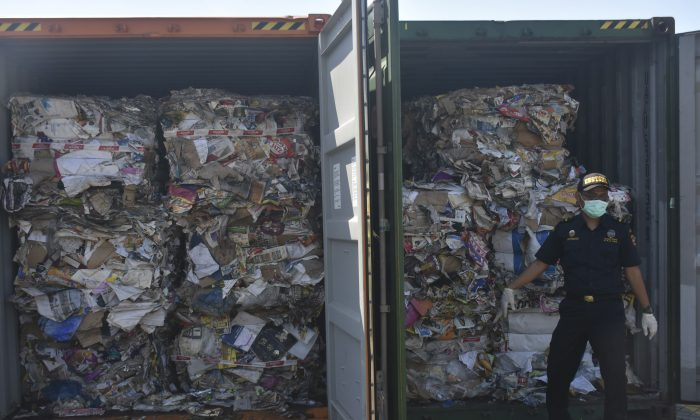 Custom officers stand near containers of waste at Tanjung Perak port in Surabaya, East Java, Indonesia, Tuesday, Jul. 9, 2019. (AP Photo)