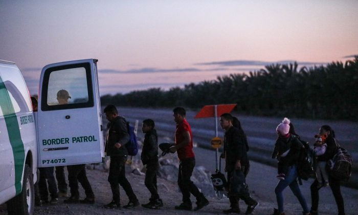 A group of illegal aliens is loaded into a Border Patrol van after crossing from Mexico into Yuma, Ariz., on April 12, 2019. (Charlotte Cuthbertson/The Epoch Times)