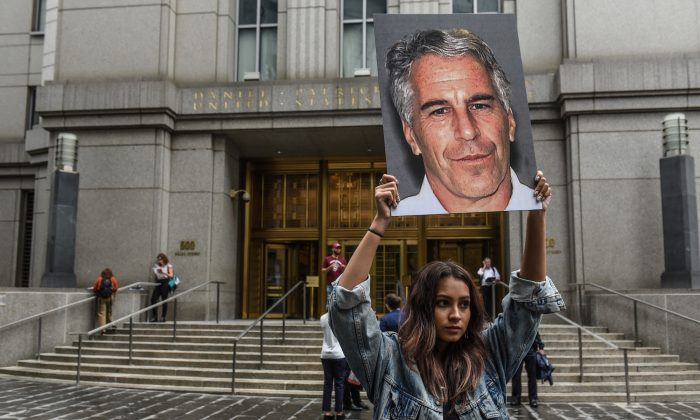 "A protest group called ""Hot Mess"" hold up signs of Jeffrey Epstein in front of the federal courthouse in New York City on July 8, 2019. (Stephanie Keith/Getty Images)"