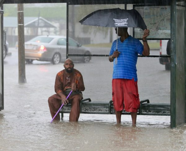 Residents sit under a bus shelter