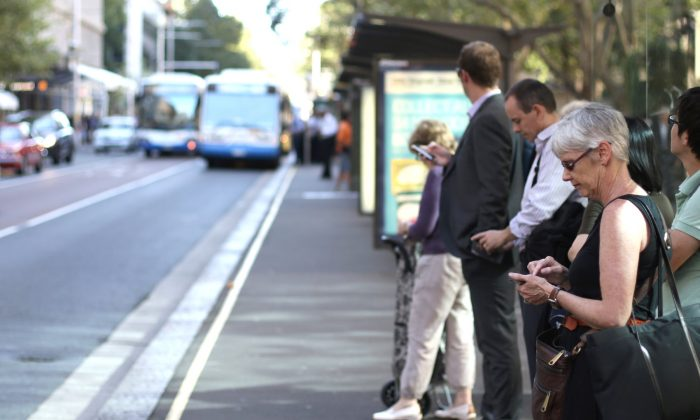 People wait at a bus stop in Sydney, Australia, on Feb, 19, 2013. (Mark Kolbe/Getty Images)