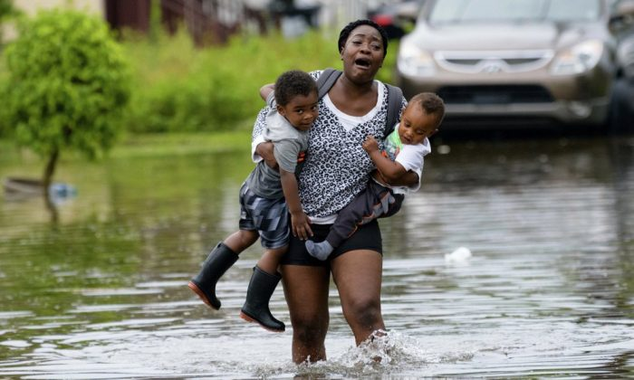 Terrian Jones reacts as she feels something moving in the water at her feet as she carries Drew and Chance Furlough to their mother on Belfast Street in New Orleans during flooding from a storm in the Gulf Mexico that dumped lots of rain on July 10, 2019. (Matthew Hinton/AP Photo)