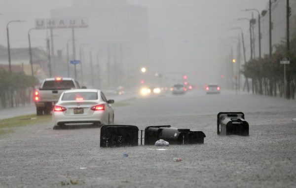 Vehicles head down a flooded Tulane Ave