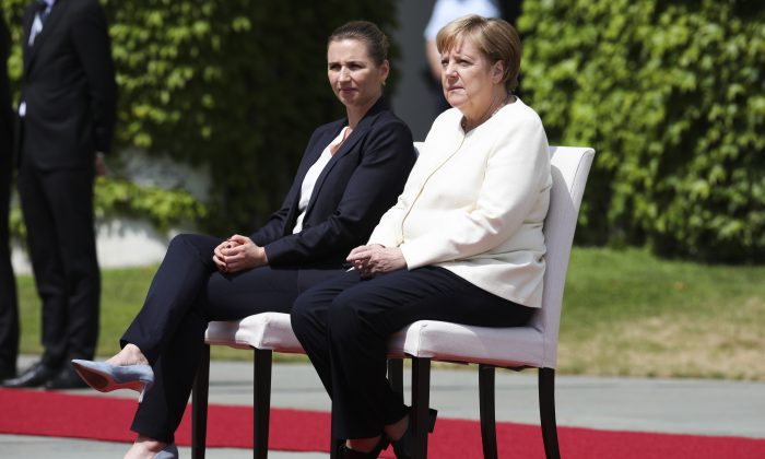 German Chancellor Angela Merkel (R) and Danish Prime Minister Mette Frederiksen, sit on chairs as they listen to the national anthems prior to a meeting at the chancellery in Berlin, Germany, on July 11, 2019. (Markus Schreiber/AP Photo)