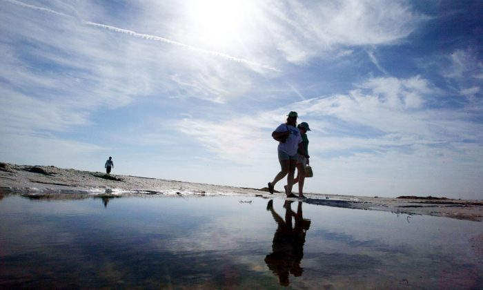 People walk on the beach on Sanibel Island, which neighbors Captiva, on Aug. 18, 2004. (Mario Tama/Getty Images)