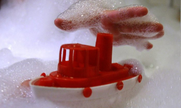 A child in a foam bath in a bath tub reaches for a plastic toy in a file photo. (Alexander Hassenstein/File Photo/Getty Images)