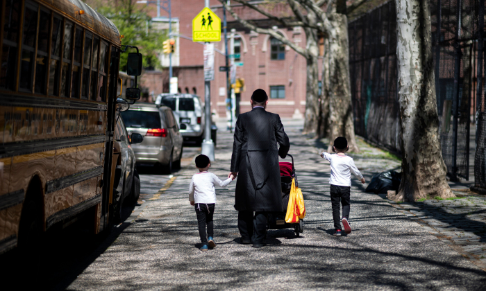 A Jewish man walks with his children down a street in a Jewish quarter in Williamsburg Brooklyn in New York City on April 24, 2019. (Johannes Eisele/AFP/Getty Images)