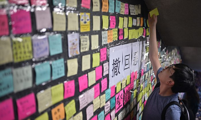 "A man reaches up to place a handwritten note onto a makeshift ""Lennon Wall"" near a footbridge in Hong Kong on July 11, 2019. (Anthony WALLACE/AFP/Getty Images)"
