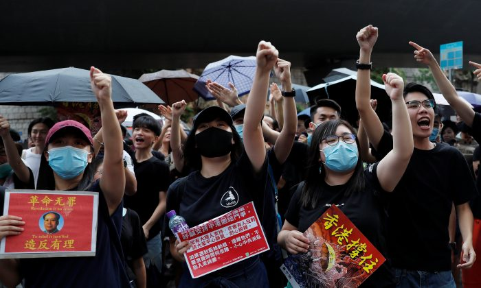 Anti-extradition bill protesters shout slogans to Chinese tourists during a march to West Kowloon Express Rail Link Station in Hong Kong, China on July 7, 2019. (Tyrone Siu/Reuters)