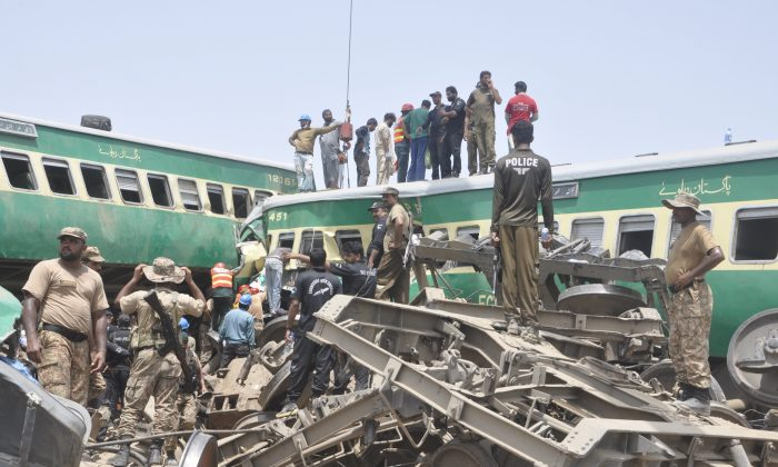 Pakistani officials and volunteers work at a train crash site in Rahim Yar Khan, Pakistan on July 11, 2019. (Waleed Saddique/AP)