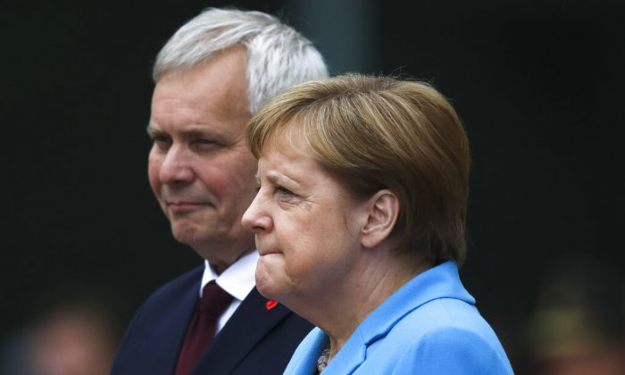 German Chancellor Angela Merkel and Prime Minister of Finland Antti Rinne listen to the national anthems during the welcoming ceremony at the chancellery in Berlin, Germany, on July 10, 2019. (Markus Schreiber/AP Photo)
