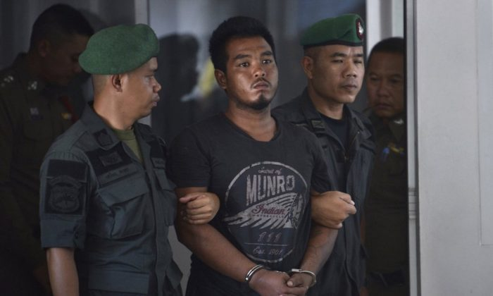 Thai suspect Ronnakorn Romruen, 23 years old, is escorted by police as he arrives at the Koh Sichang police station in Chonburi province, Thailand, Monday, April 9, 2019. (AP Photo)