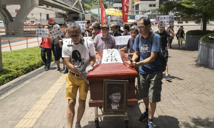 "Protesters carry a mock coffin of city leader Carrie Lam as they parade against a controversial extradition bill around the government headquarters in Hong Kong on July 12, 2019. Lam on July 9 declared the legislation ""dead,"" but protesters insist that she formally withdraw the bill and quit. (Li Yi/The Epoch Times)"