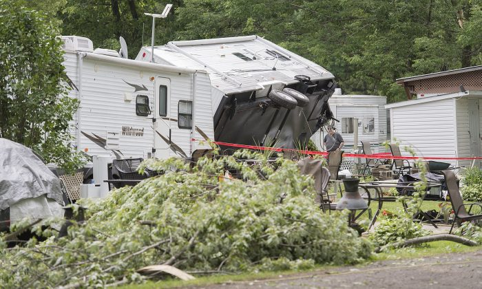 An overturned trailer and fallen trees are shown following a storm at a campground in Saint-Roch-de-l'Achigan, near Montreal, Que., on July 12, 2019. (Graham Hughes/The Canadian Press)