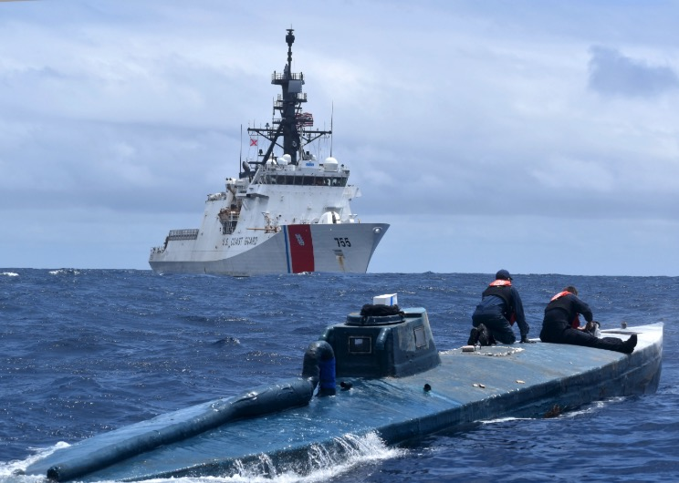 Crew members of the U.S. Coast Guard Cutter Munro inspect a self-propelled semi-submersible suspected drug smuggling vessel (SPSS) in international waters of the Eastern Pacific Ocean, on June 19, 2019. (U.S. Coast Guard Photo)