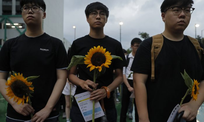 Attendees take part in a public memorial for Marco Leung, a 35-year-old man who fell to his death weeks ago after hanging a protest banner against an extradition bill, in Hong Kong, China on July 11, 2019. The parents of Leung have urged young people to stay alive to continue their struggle. (Kin Cheung/AP)