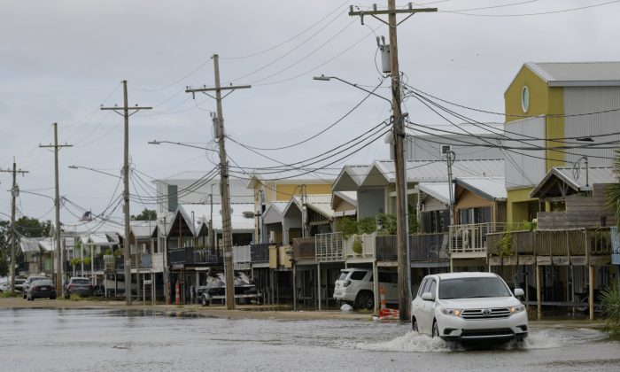 An SUV travels down Breakwater Drive in New Orleans, La., July 12, 2019, near the Orleans Marina as water moves in from Lake Pontchartrain from the storm surge from Tropical Storm Barry in the Gulf of Mexico. The area is behind a flood wall that protects the rest of the city. (AP Photo/Matthew Hinton)