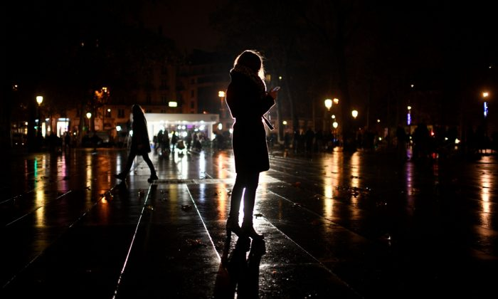 A woman on a phone at night. (Martin Bureau/AFP/Getty Images)