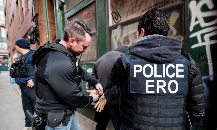 In this undated image provided by Immigration and Customs Enforcement, immigration officers arrest and illegal alien for removal. (Public Domain)