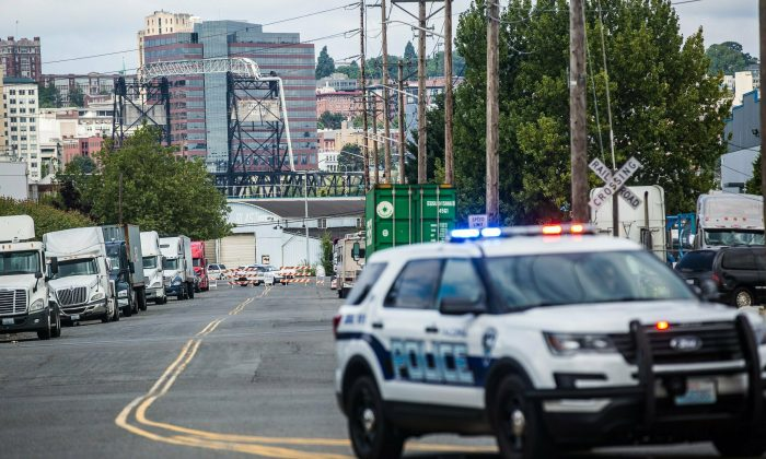 A police officer guards the front of a road block near the Northwest Detention Center in Tacoma, Wash. on July 13, 2019. (Rebekah Welch/The Seattle Times via AP)