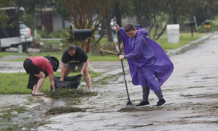 Residents clean up pine branches deposited from Tropical Storm Barry, in front of their houses in Morgan City, La., on July 13, 2019. (Rogelio V. Solis/AP Photo)