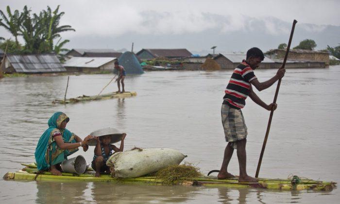 Flood effected villagers move on a makeshift bamboo raft in Katahguri village along the river Brahmaputra, east of Gauhati, India on July 14, 2019. (Anupam Nath/AP)