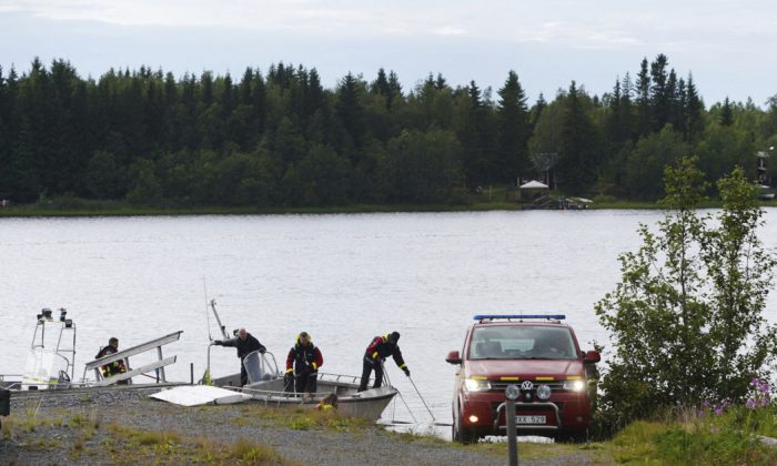 Emergency services attend the accident site at a small harbor at Ume river, outside Umea, Sweden on July 14, 2019. (Samuel Pettersson/TT via AP)