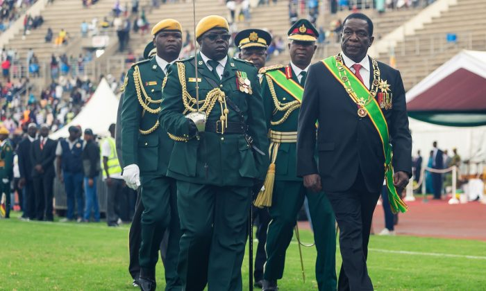 Zimbabwe's President Emmerson Mnangagwa (R) at the country's National Sports Stadium on April 18, 2019. JEKESAI NJIKIZANA/AFP/Getty Images