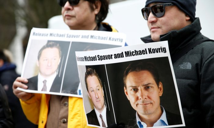 People hold signs calling for China to release Canadians Michael Spavor and Michael Kovrig during an extradition hearing for Huawei executive Meng Wanzhou at the B.C. Supreme Court in Vancouver on March 6, 2019. (Lindsey Wasson/Reuters)