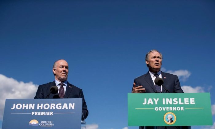 British Columbia Premier John Horgan, left, listens as Washington State Gov. Jay Inslee speaks during a news conference about high speed rail, in Vancouver, B.C., on March 16, 2018. (Darryl Dyck/The Canadian Press)