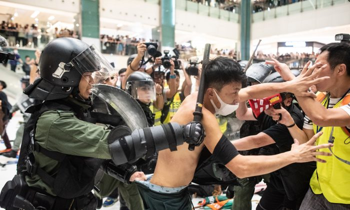 Police officers tear the shirt of a protester during a clash inside a shopping arcade after a rally against a controversial extradition bill in Sha Tin district of Hong Kong on July 14, 2019. (PHILIP FONG/AFP/Getty Images)