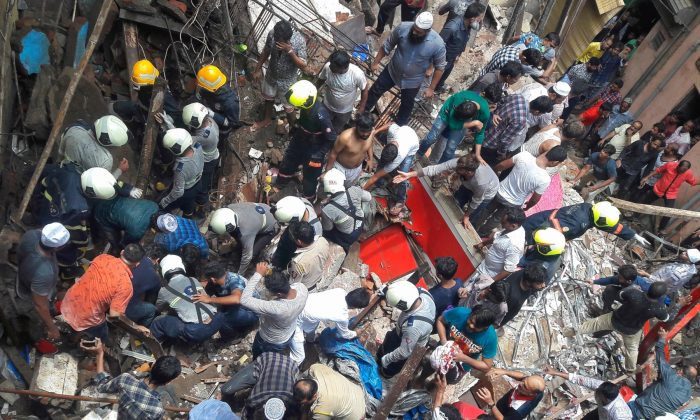 Rescue workers and residents search for survivors at the site of a collapsed building in Mumbai, India on July 16, 2019. (Stringer/Reuters)