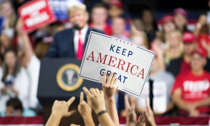 "An attendee holds a ""Keep America Great"" sign as President Donald Trump speaks to the crowd during a campaign rally at Freedom Hall in Johnson City, Tennessee, on Oct. 1, 2018. (Sean Rayford/Getty Images)"
