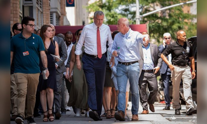 New York Mayor Bill de Blasio, center left, listens to Con Ed President Tim Cawley, July 14, 2019, as the mayor visits the site of the power outage on July 13, on New York's Upper West Side. (Michael Appleton/Mayoral Photography Office via AP)
