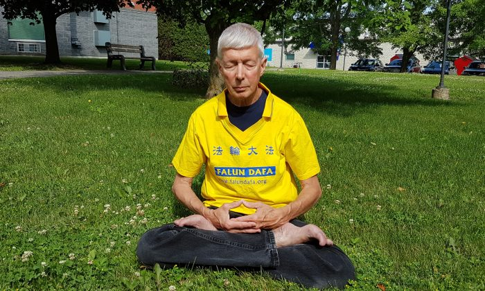 Falun Gong practitioner Gerry Smith, seen here meditating in a park, was ordered by the CEO of the Ottawa Dragon Boat Festival to remove his T-shirt bearing the name of his spiritual practice on June 22, 2019, at the festival. John Brooman told Smith that the Chinese Embassy is a sponsor of the festival and  didn't want Falun Gong adherents at the event. (The Epoch Times)