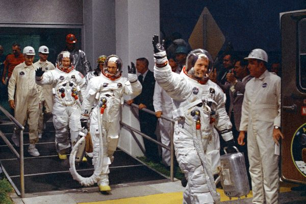 Neil Armstrong, Michael Collins and Buzz Aldrin walk to the van