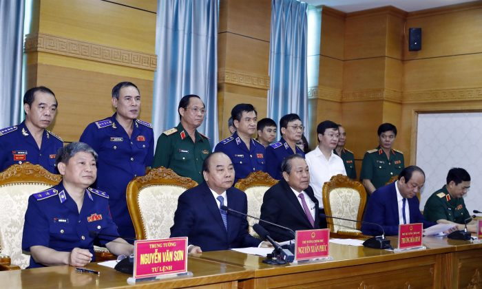 Vietnam's Prime Minister Nguyen Xuan Phuc (2nd L, front) and Deputy Prime Minister Truong Hoa Binh (2nd R, front) speaks with sailors of Coast Guard Force on field via video call during their visit to Coast Guard Command in Hanoi, Vietnam on July 11, 2019. (Thong Nhat/VNA via Reuters)