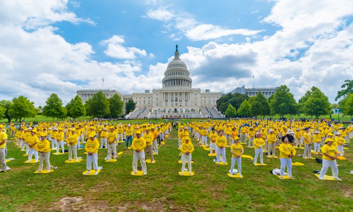 Falun Gong practitioners perform the exercises at a rally commemorating the 20th anniversary of the persecution of Falun Gong in China, on the West Lawn of Capitol Hill on July 18, 2019. (Mark Zhou/The Epoch Times)