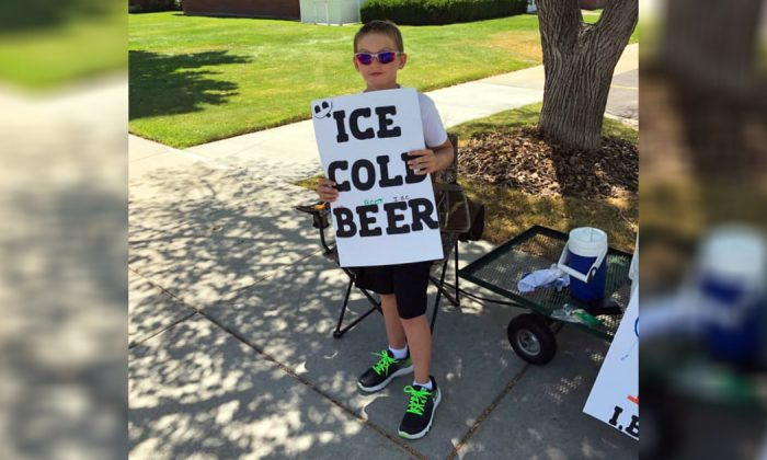 "An underage child holds a sign advertising what appears to be ""ice cold beer"" in Brigham, Utah, on July 16, 2019. (Brigham City Police Department)"