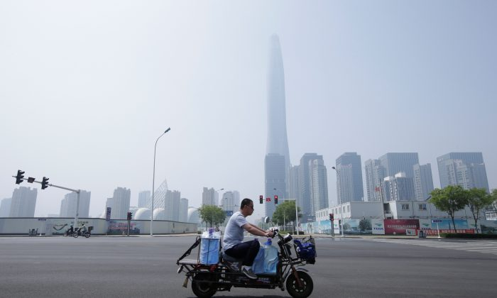 A man rides an electric motorcycle carrying water past Chow Tai Fook Financial Center in Tianjin's Binhai new district, China on May 16, 2019. (Jason Lee/Reuters)