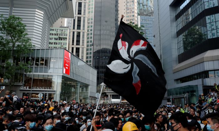 People hold up a black flag during a protest outside police headquarters to demand Hong Kong's leaders step down and withdraw an extradition bill, in Hong Kong, China on June 21, 2019. (Tyrone Siu/Reuters)